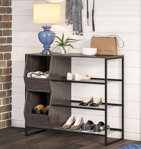 Two gray wood colored open bins next to three black metal shoe shelves with storage space on top