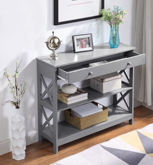 A light gray console table with two shelves and one large top drawer