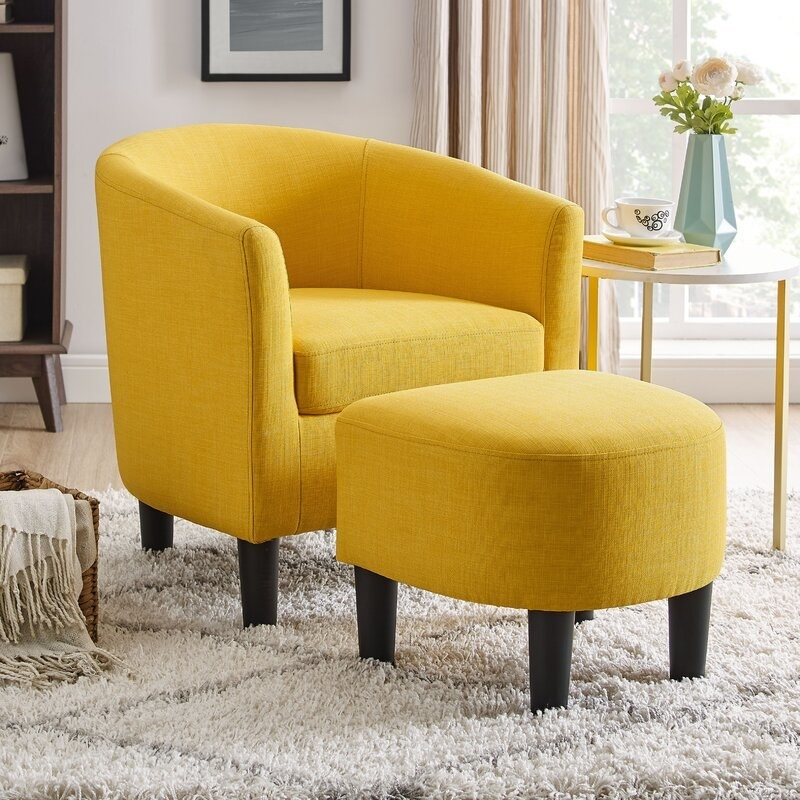 A yellow chair and ottoman with dark wooden legs