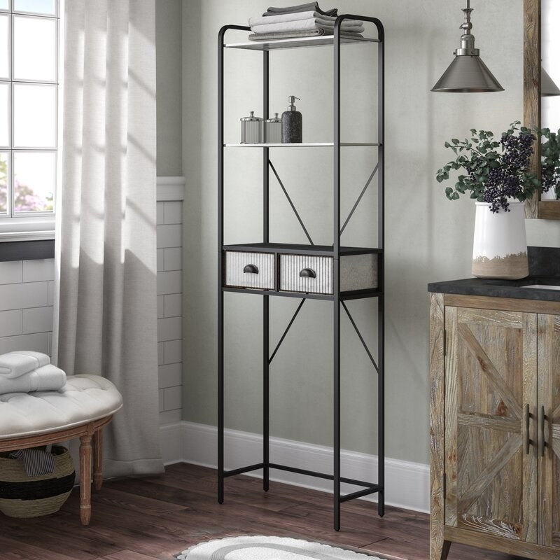 A tall, thin black framed etagere with two small drawers in the middle and two shelves above