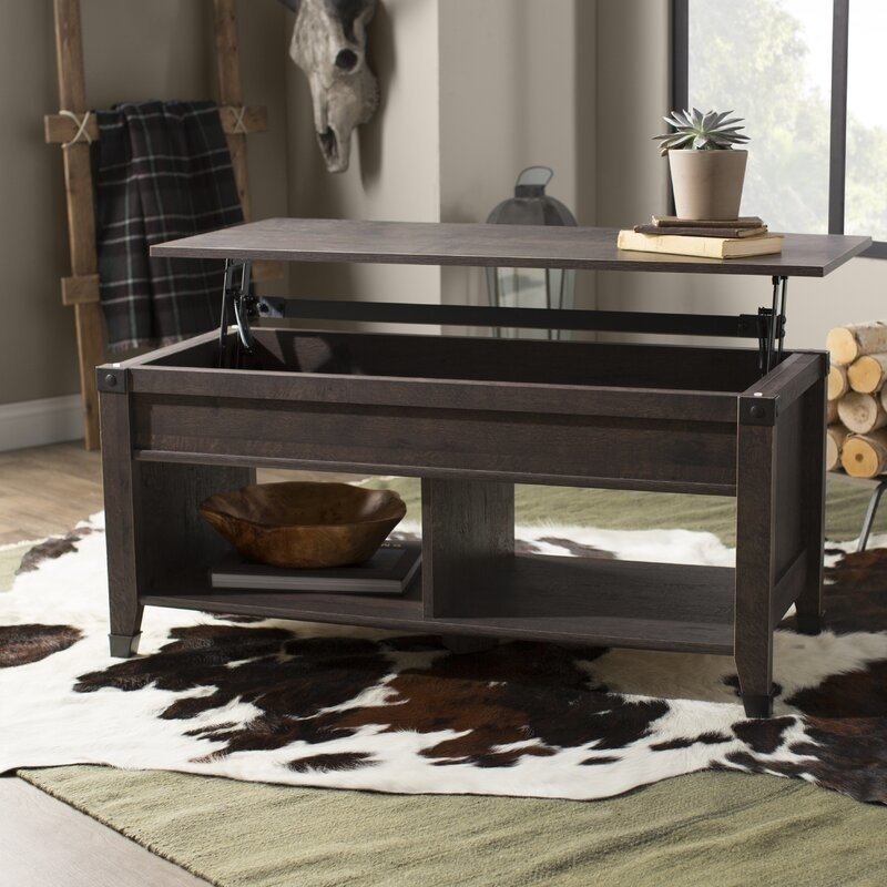 A birchwood-colored coffee table with two open bottom shelves and a lift top to reveal more storage