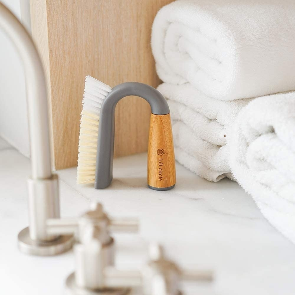 A grout scrubber on a counter next to a faucet and towels