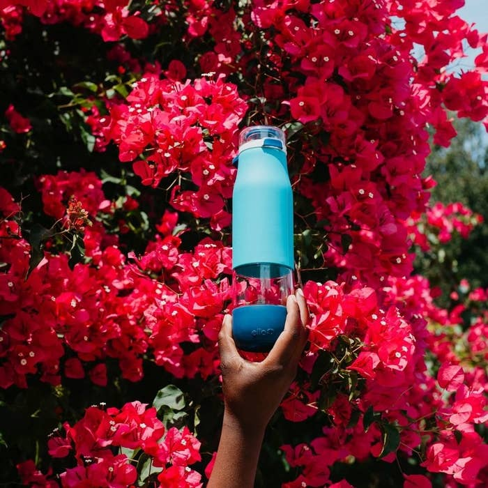 A person holding a water bottle against a wall of flowers