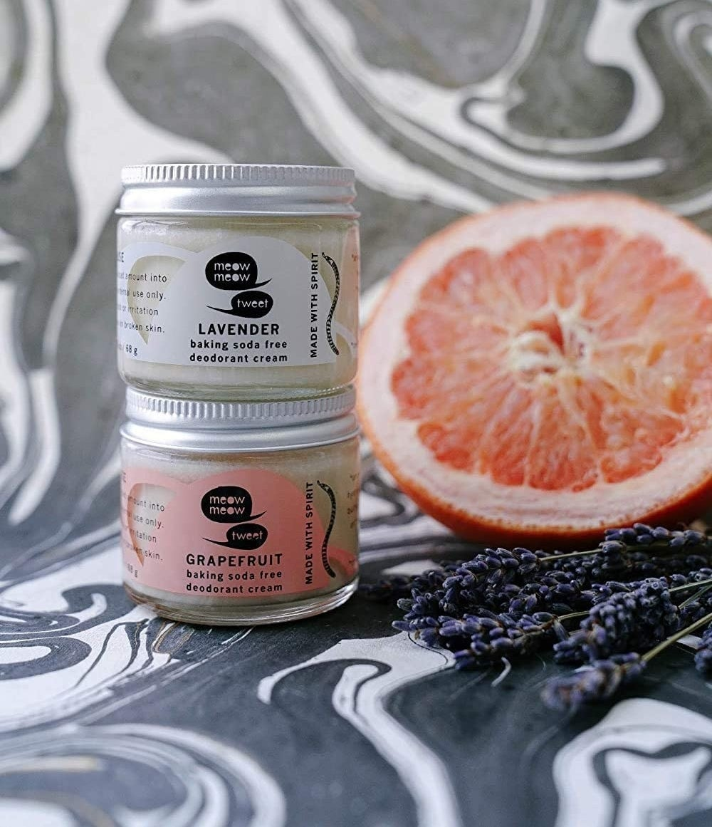 A tub of lavender deodorant cream on top of a tub of grapefruit deodorant cream