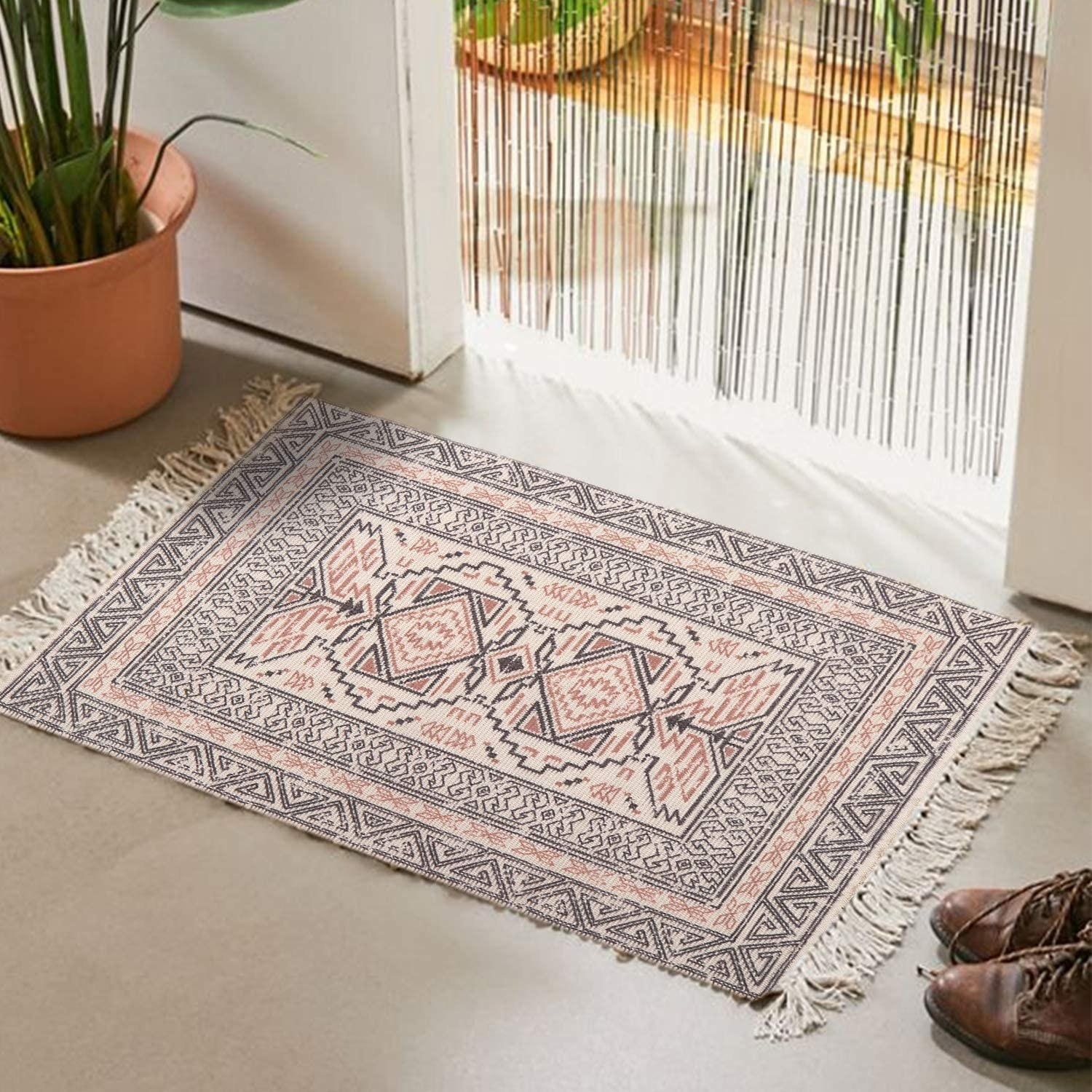 The rectangle rug with fringe on either side and a boho pattern in black and red inside