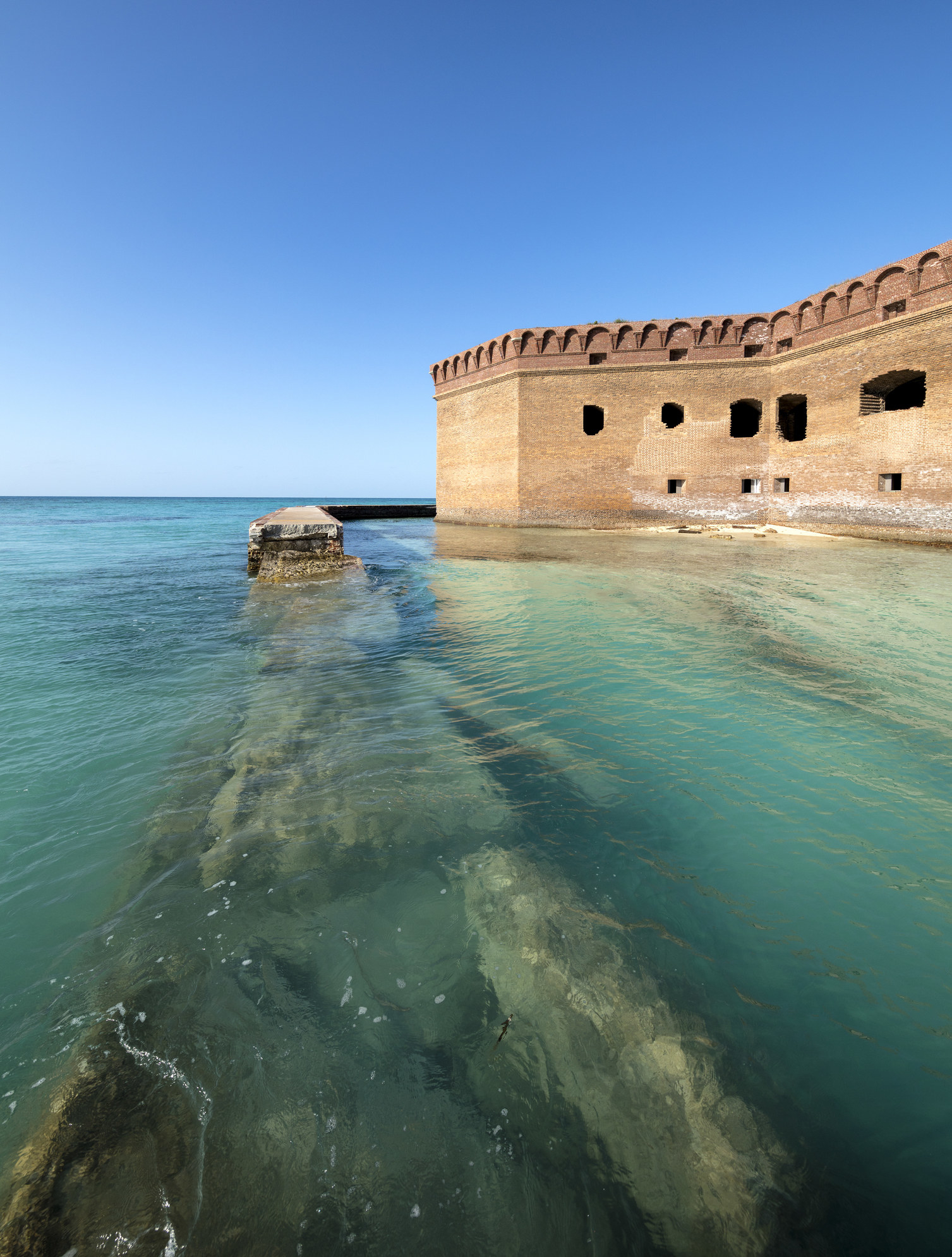 A view of Fort Jefferson and a moat surrounded by clear blue water at Dry Tortugas National Park.