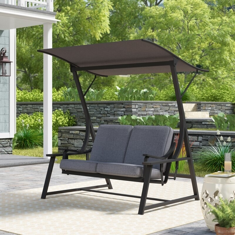 black metal frame with grey cushioned glider with large shade cover