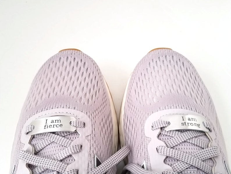 "A pair of sneakers with charms on the laces that say ""I am fierce"" and ""I am strong"""