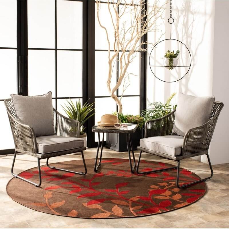 brown wicker chairs with metal legs and grey cushions with matching side table