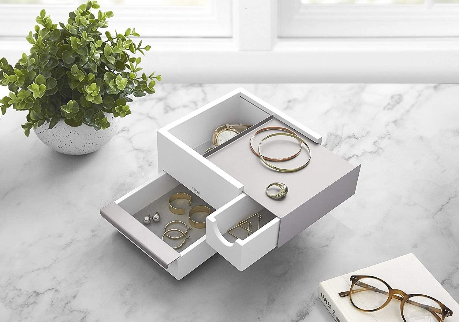 A small square jewelry box with multiple drawers of different sizes