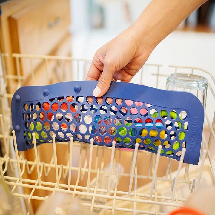 The same hand putting the product in a dishwasher, this time closed horizontally