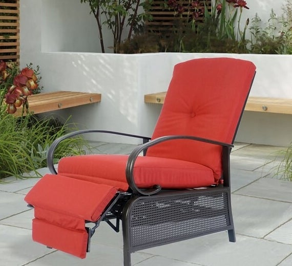 red cushioned recliner with black metal frame on patio