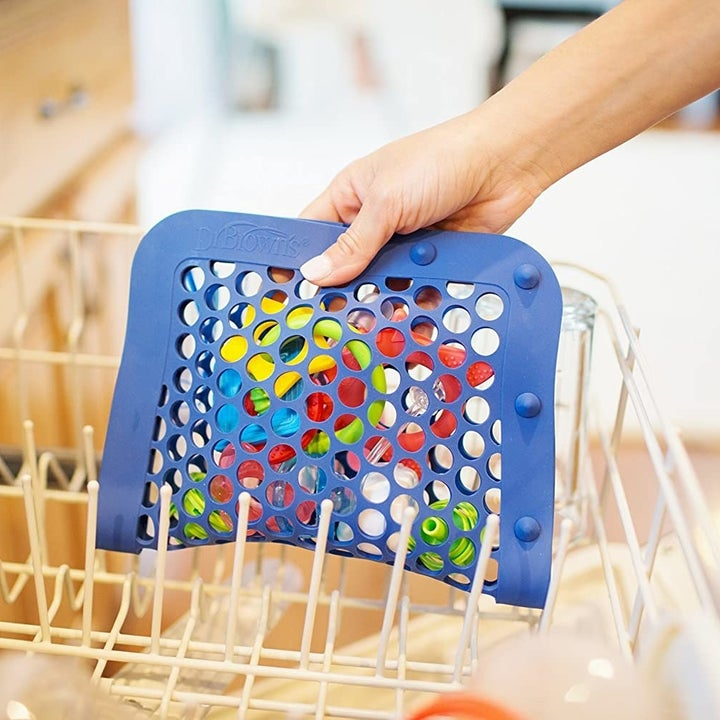 A hand putting the pouch with holes, closed vertically, in a dishwasher