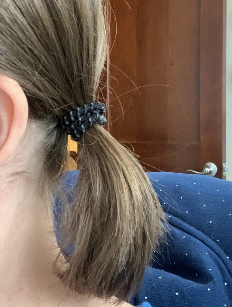A reviewer with their hair in a ponytail held by a black gripped hair tie