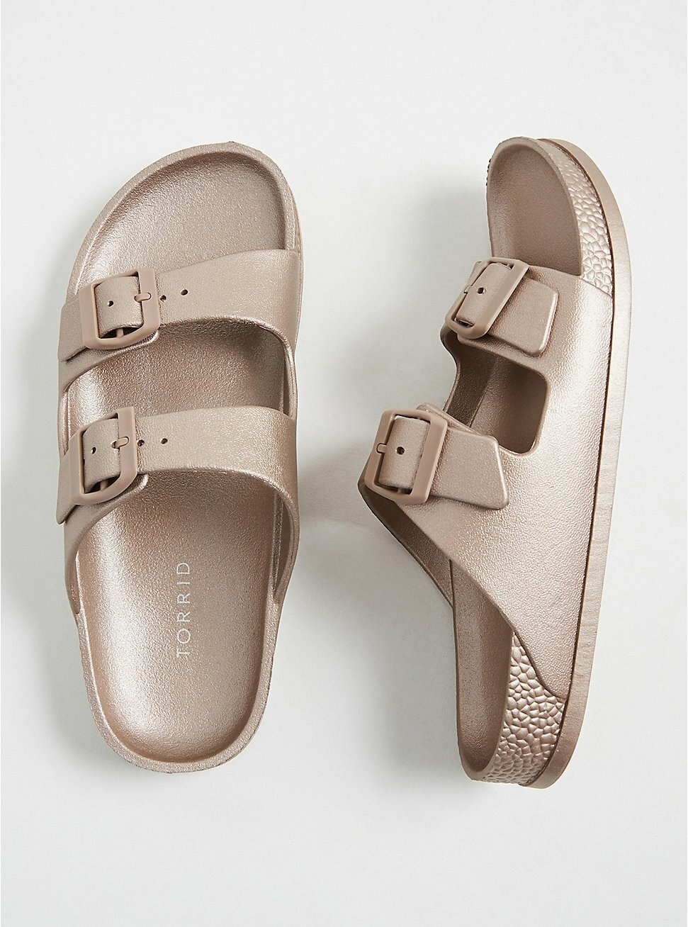 The sandals have a shimmering rose gold color, a padded rubber insole, and double top straps with buckles