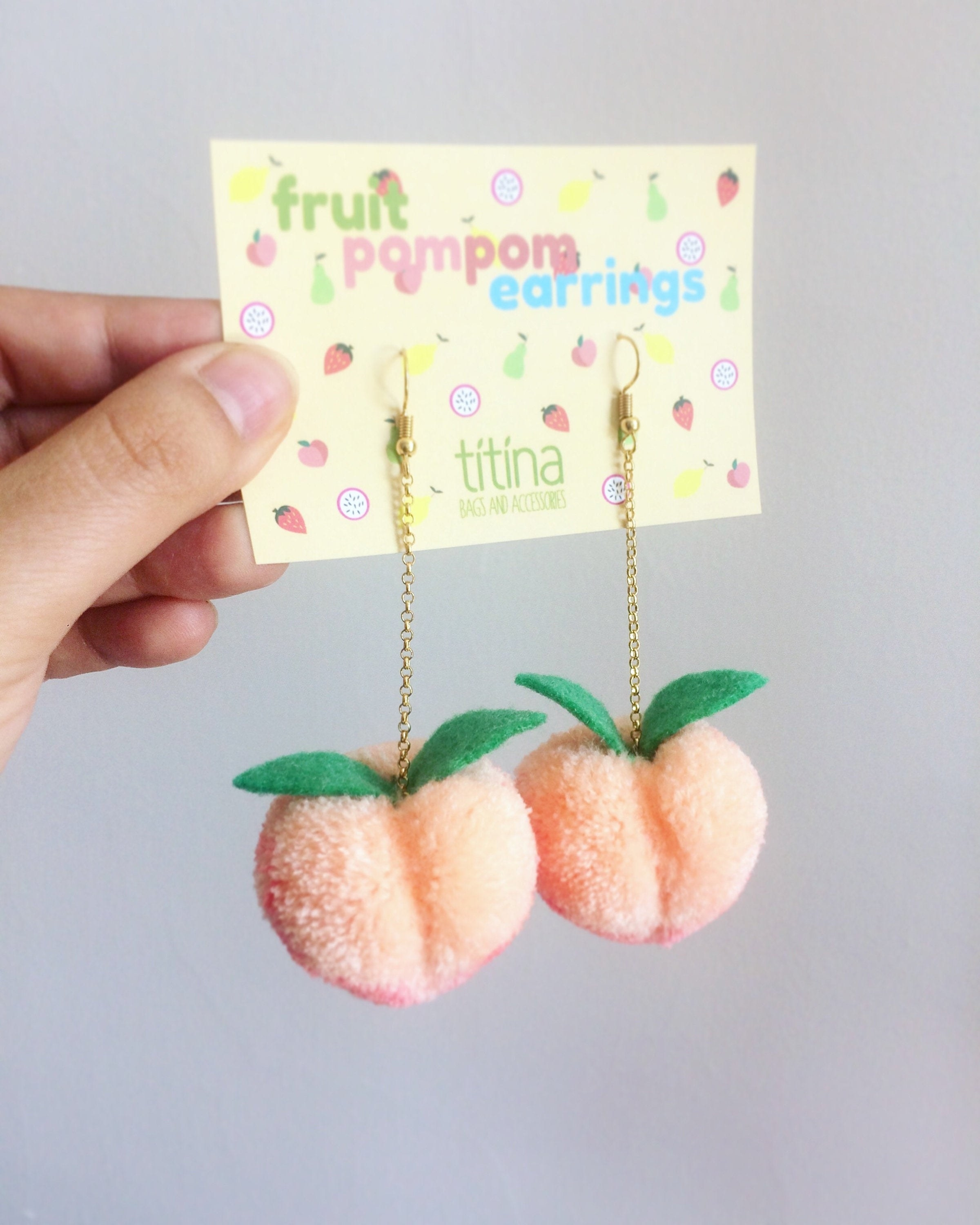 plush peach-shaped earrings in light orange and pink with two leaves on the top hanging from a gold chain