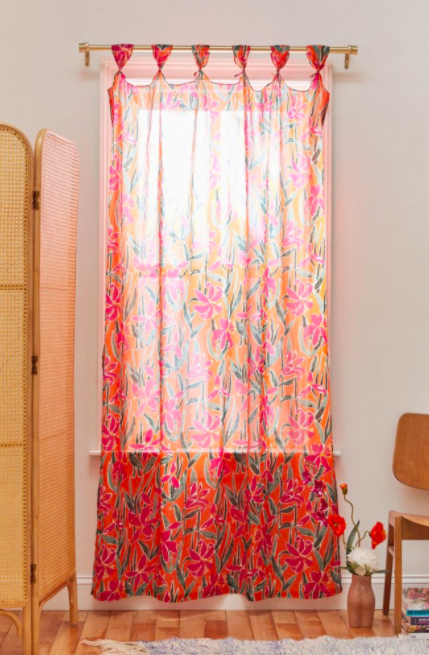 A pink and green floral knotted window panel hanging in front of an apartment window