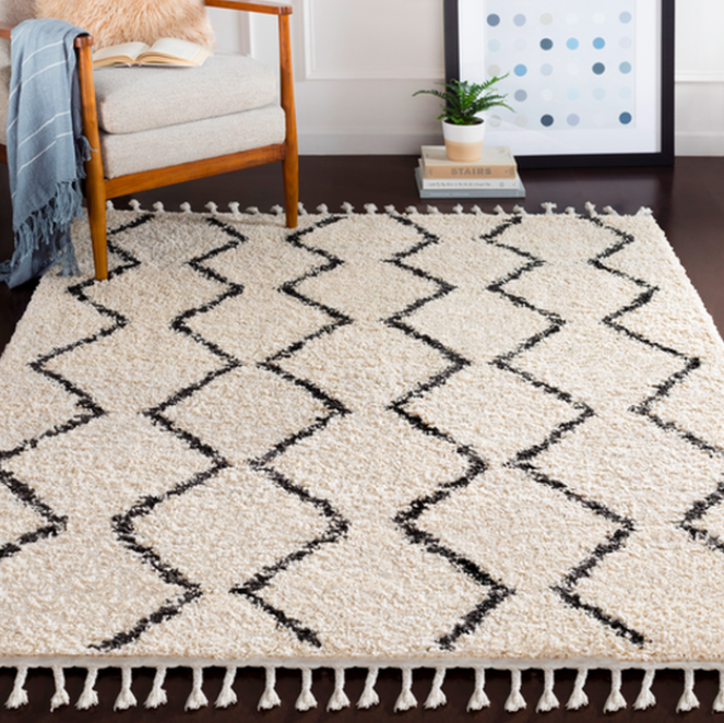 A black-and-white zig-zag patterned rug on a hardwood floor next to a chair