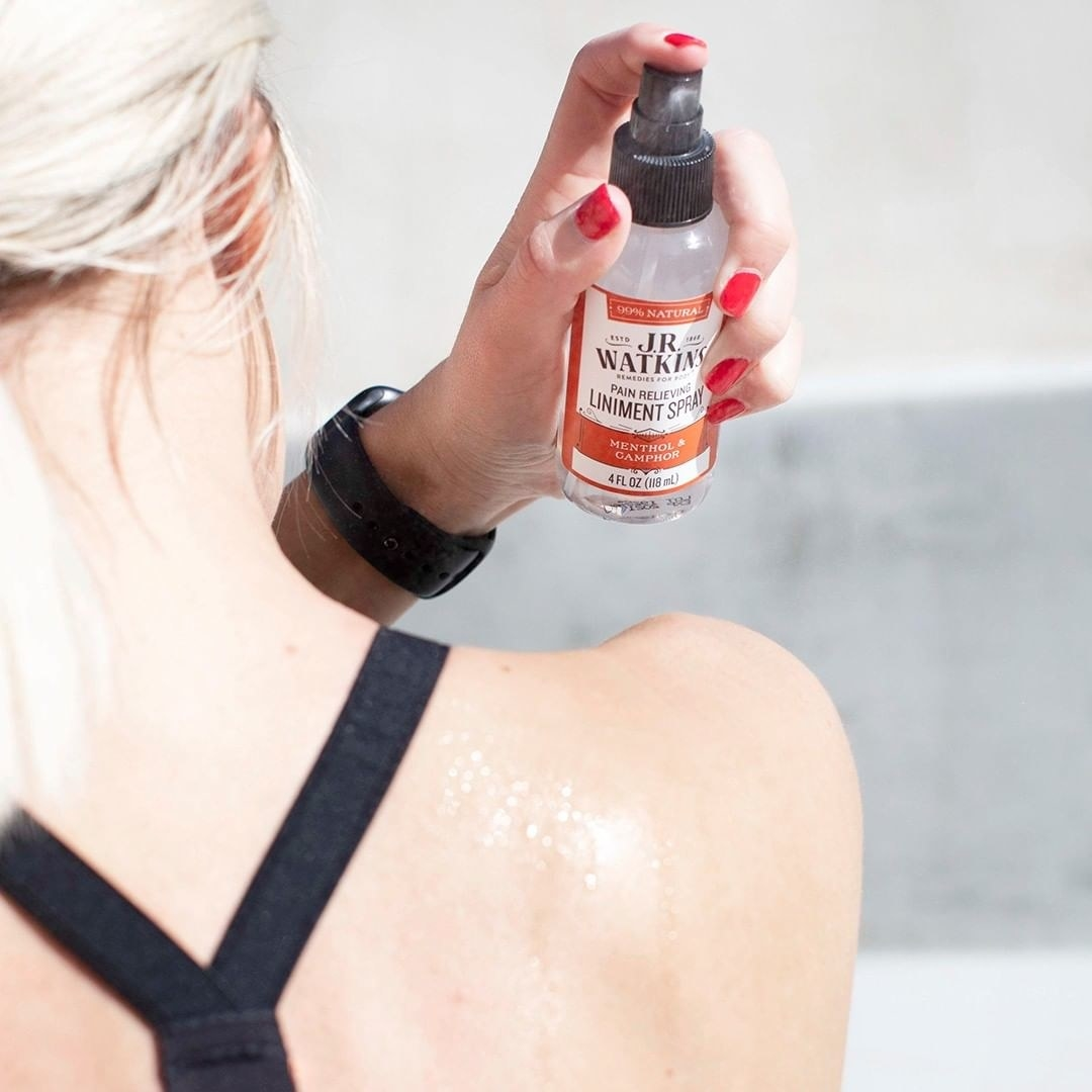 A person sprays the pain relieving spray onto their back
