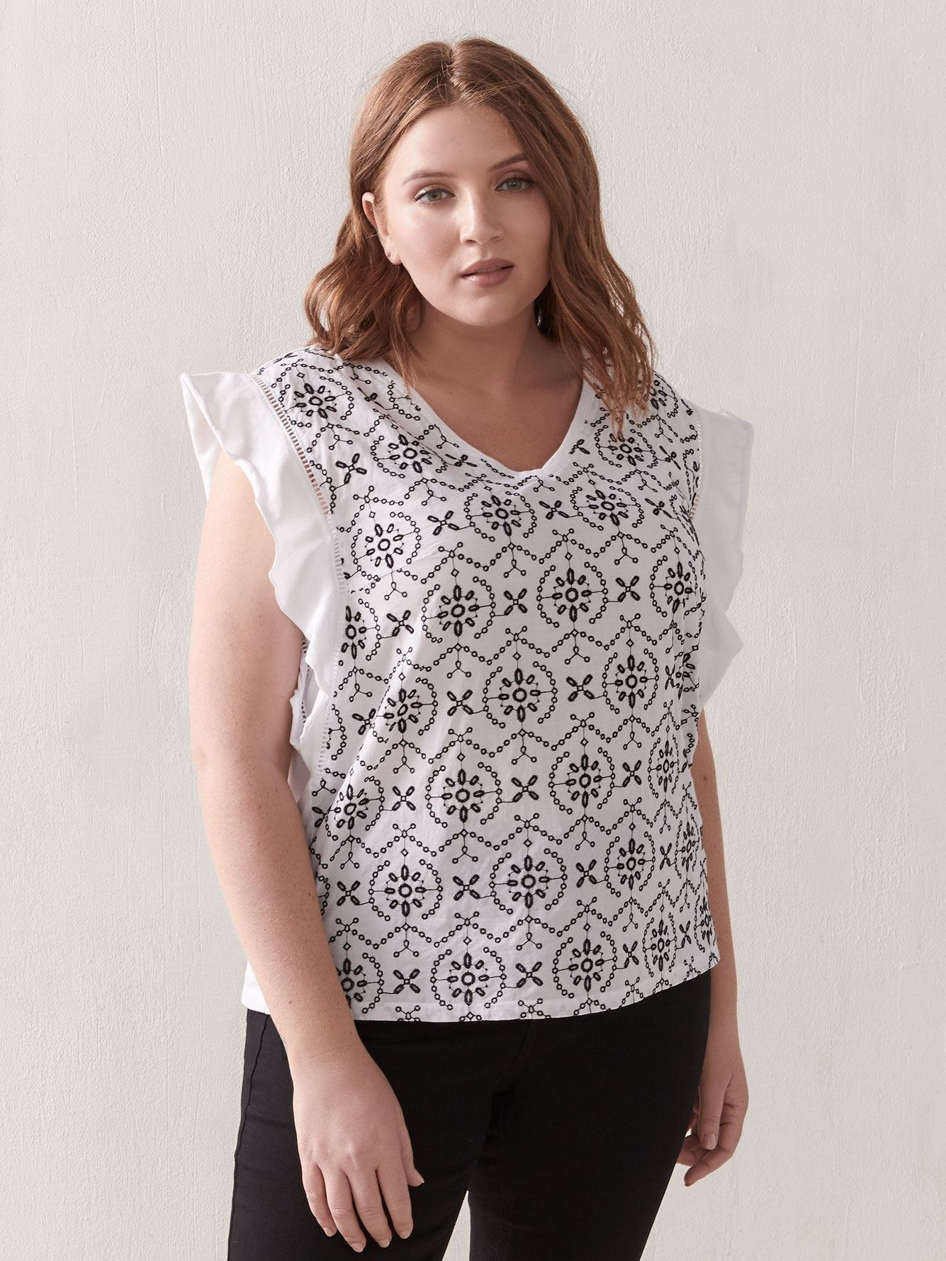Model in the black and white-patterned, sleeveless top