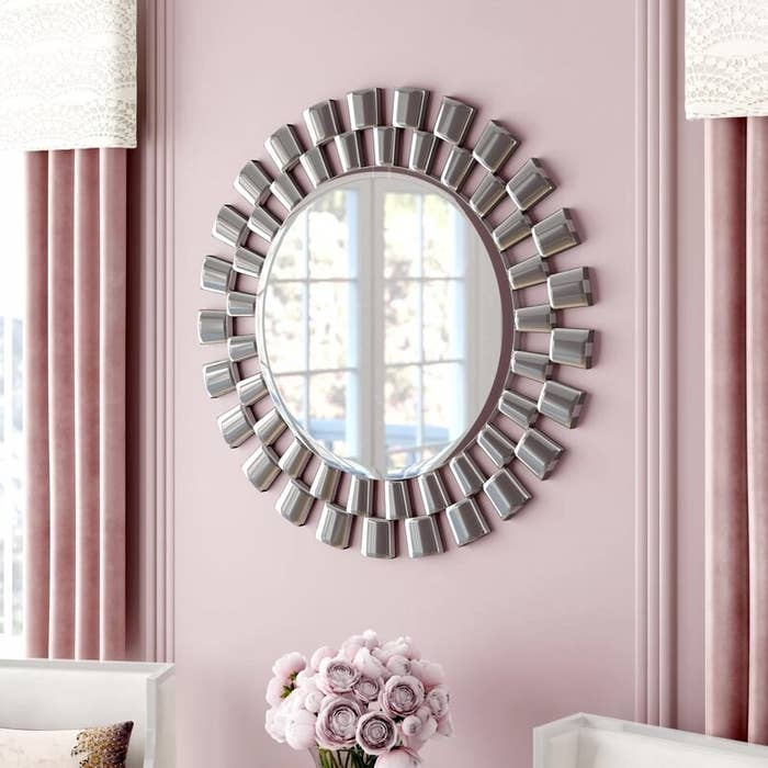 The large circular mirror with a staggered step frame