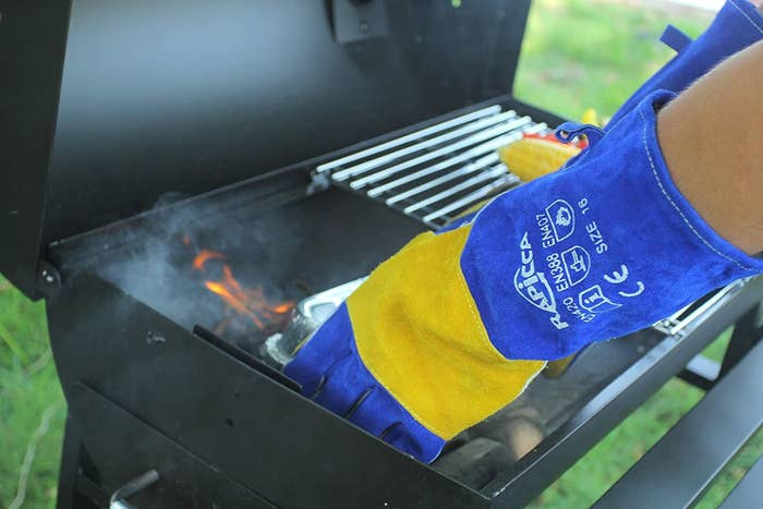 A model wearing a pair of long blue and yellow leather gloves while cooking on a grill
