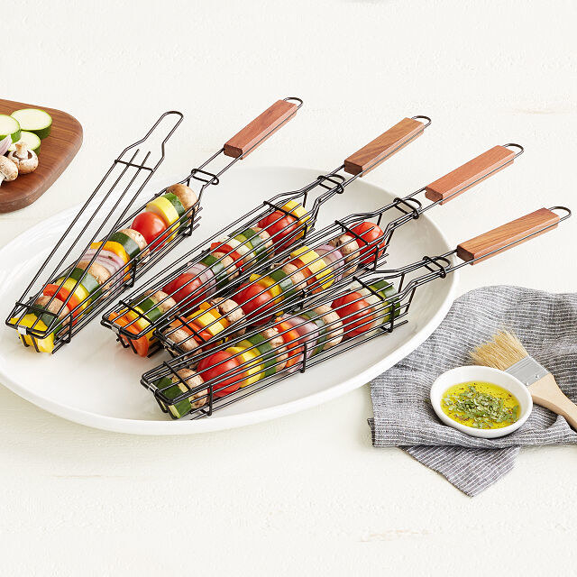 Four kabob grilling baskets laid out on a plate and filled with vegetables
