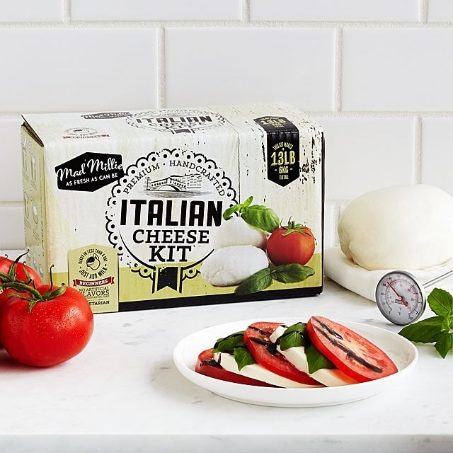 The Italian Cheese Kit sits on a countertop behind a plate with a caprese salad