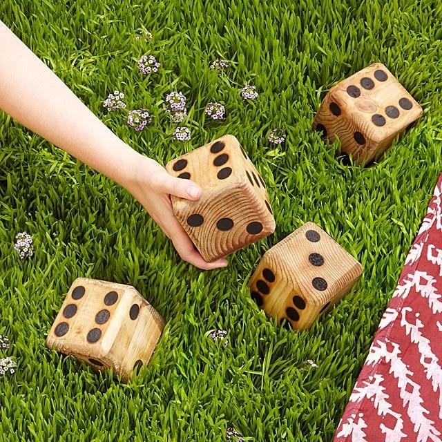 Four jumbo yard dice on grass