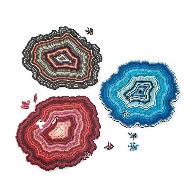 Three geode puzzles; one in pink, one in blue, one in multi
