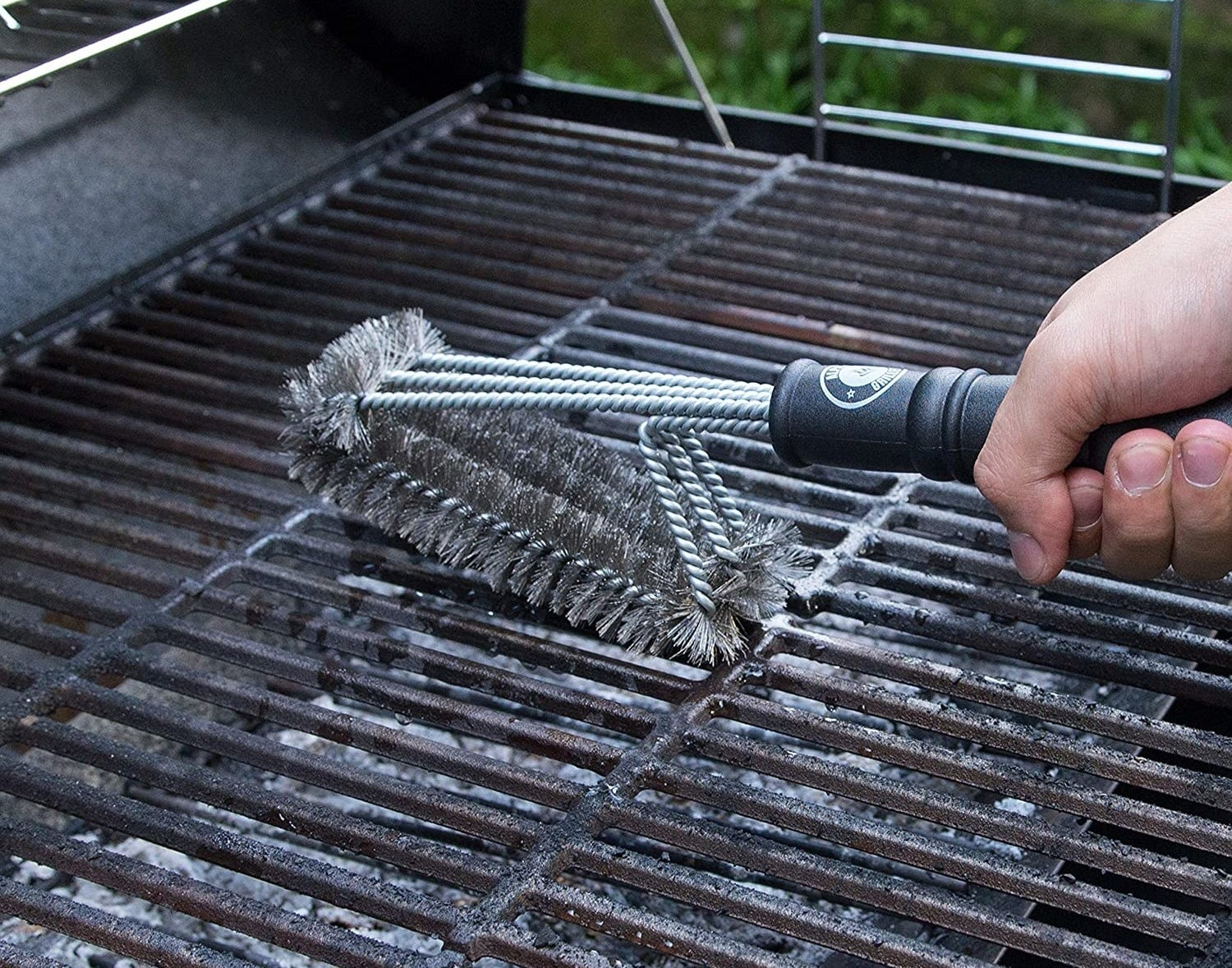 A model's hand using a black-handled silver wire brush to clean the grill