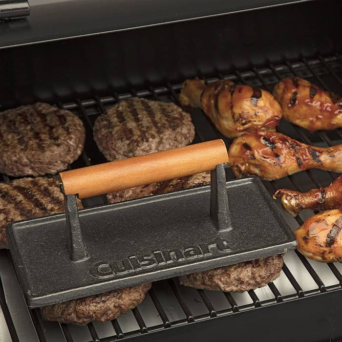 A dark-gray metal grill press the length of two hamburgers with the Cuisinart logo prominently featured