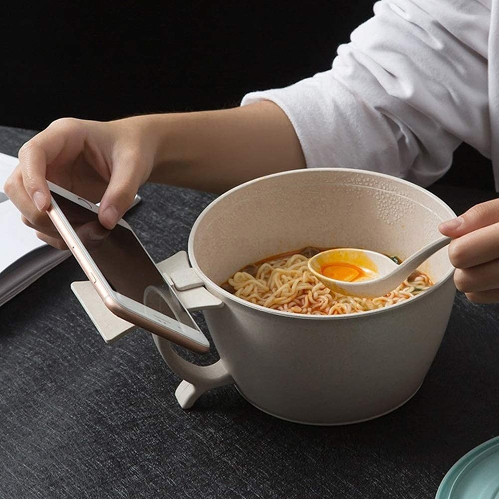 A person eating ramen while resting their phone on the built-in phone rest