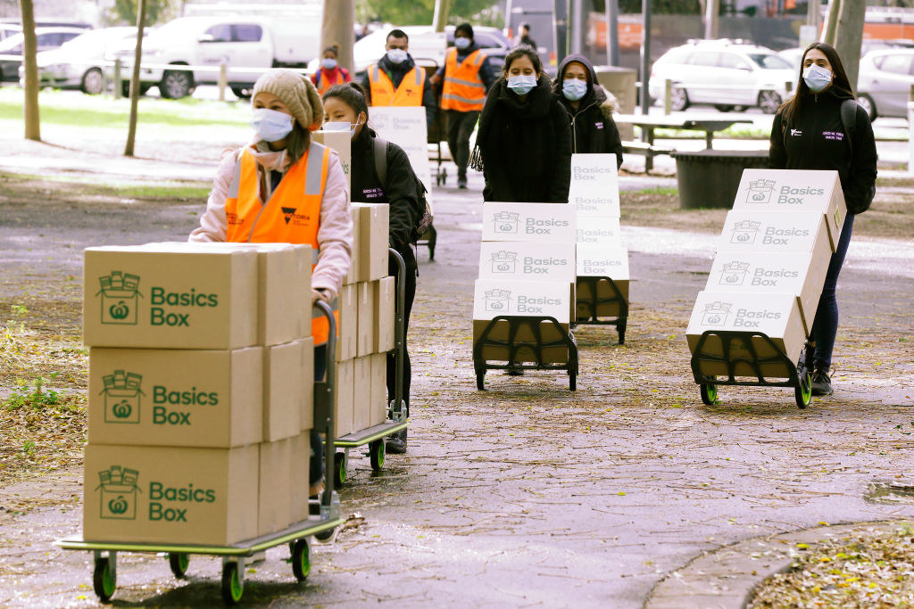 Boxes of food being delivered by volunteers wearing masks