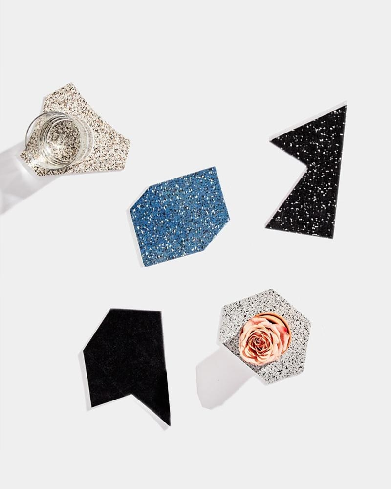 Top view of a set of five shapes on a table in black, white, and blue speckled with a glass on one and flower on another