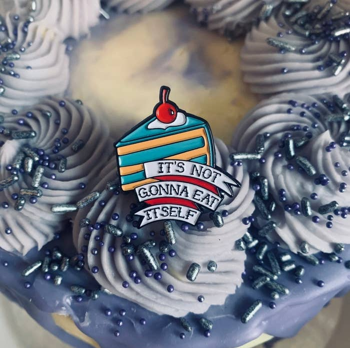 """an enamel pin of a blue and yellow slice of cake with a cherry on top that says """"it's not gonna eat itself"""""""