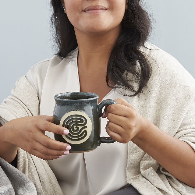 A model holds the meditation mug in one hand while the other traces the carved in labyrinth