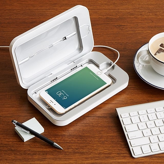 An iPhone sits inside the PhoneSoap smartphone sanitizer