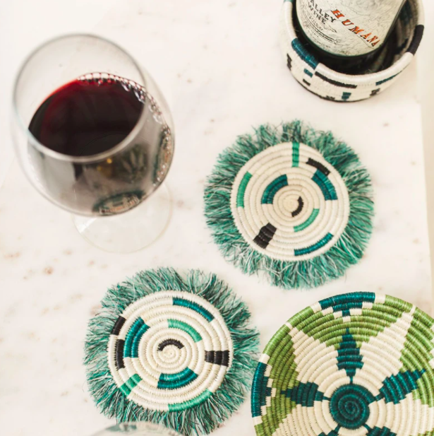 Two green fringe coasters next to a bottle of wine