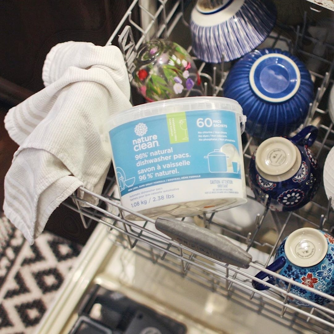 A tub of dishwasher pacs on the top level of a dishwasher