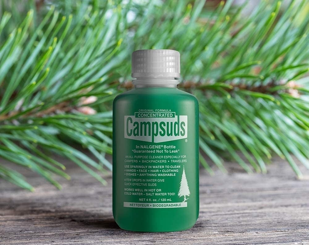 A bottle of Campsuds on a table in front of a spruce branch