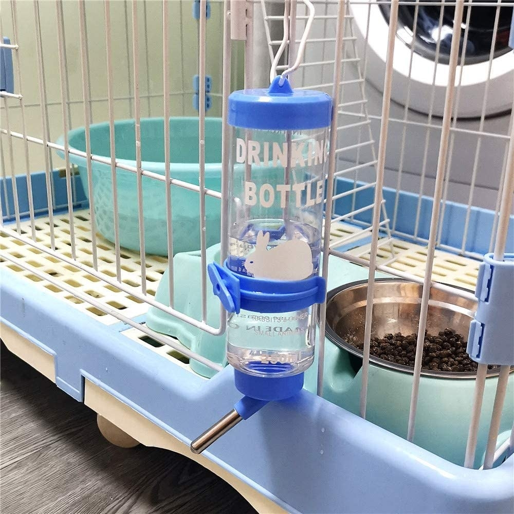 A clear water bottle with blue accents hanging from a pet cage