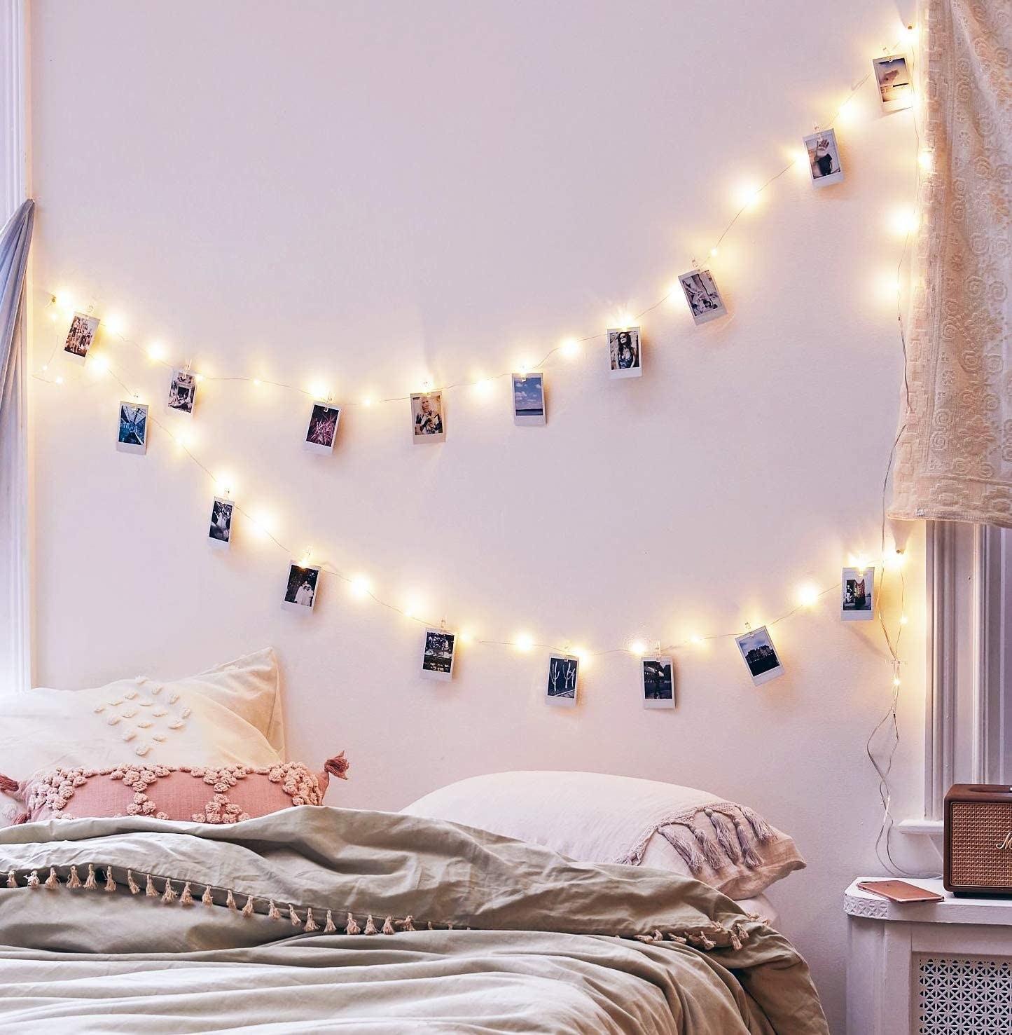 Two strings of fairy lights hanging on a wall There are small instant photos hanging from the string