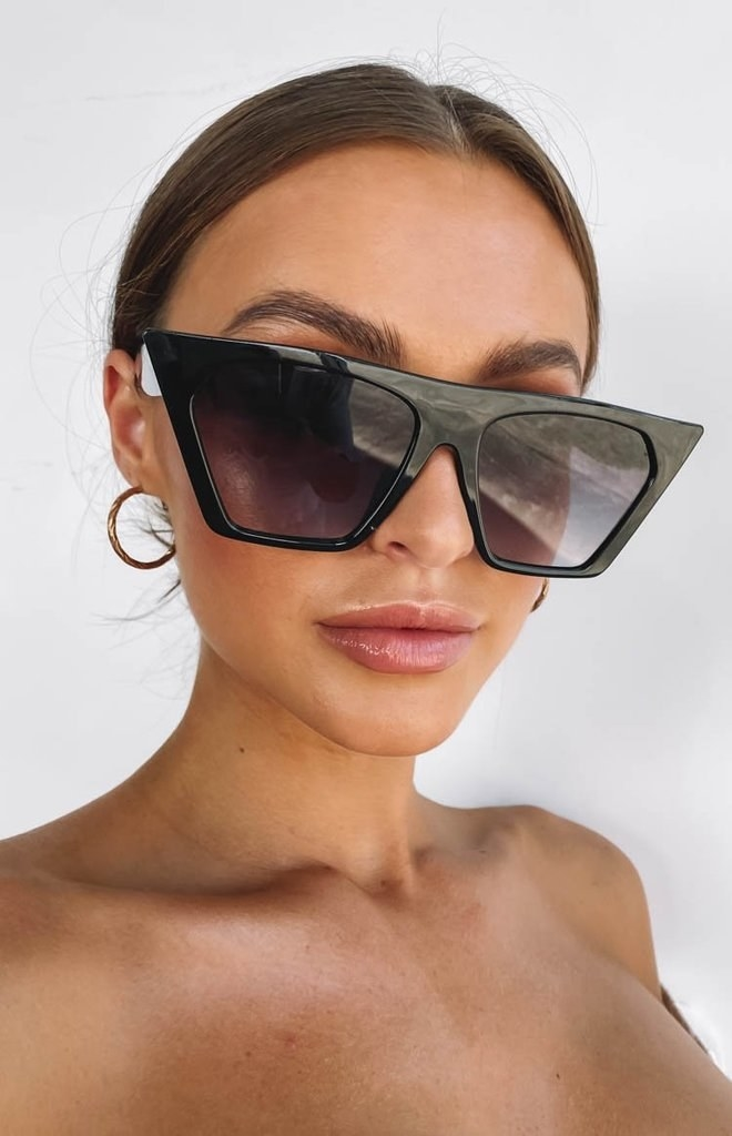 Model wearing the oversized sunglasses with wide black frames that are pointed and black lenses