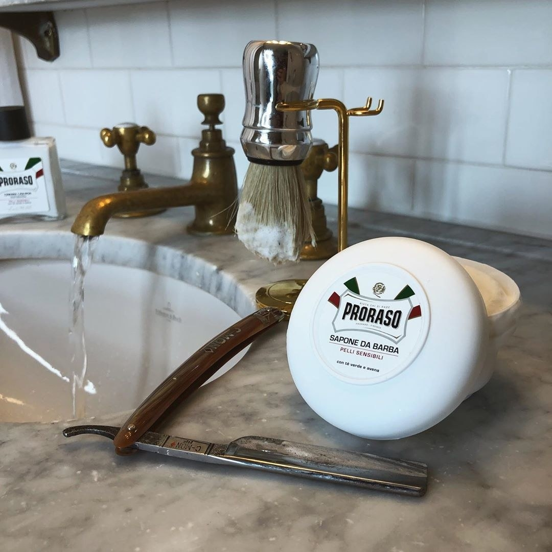 The shaving soap sits on a marble counter next to a traditional shaving brush and a straight razor