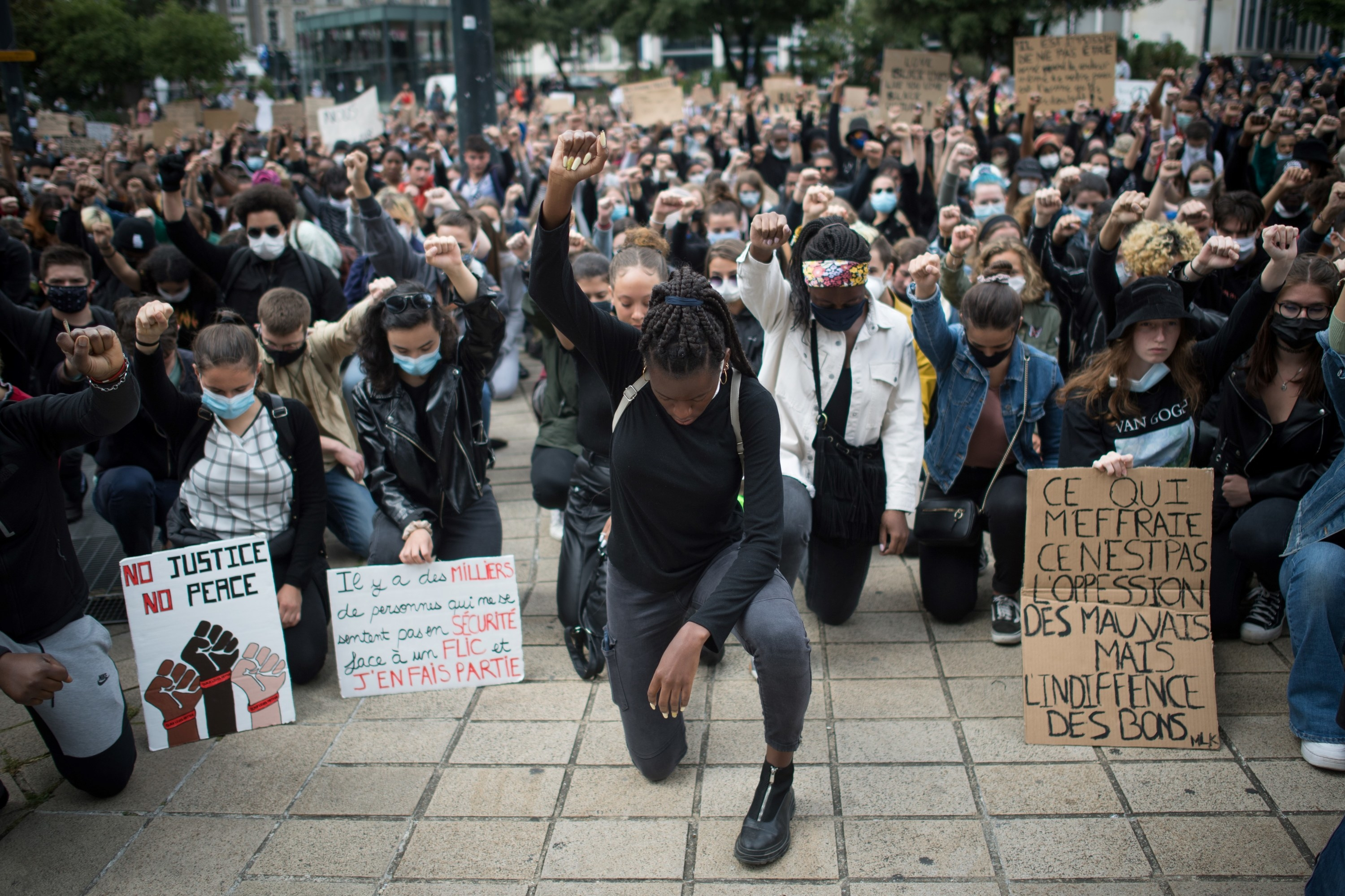 Protestors take a knee and raise their fists at a Black Lives Matter march