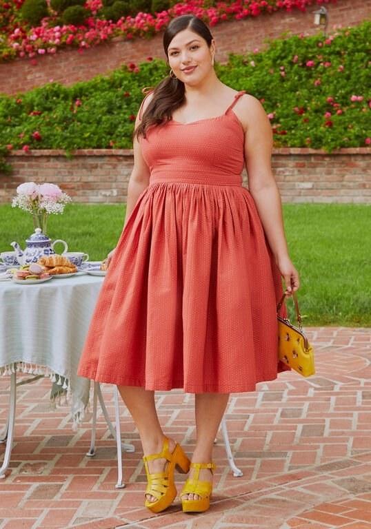 A model wearing the below-the-knee-length dress in orange