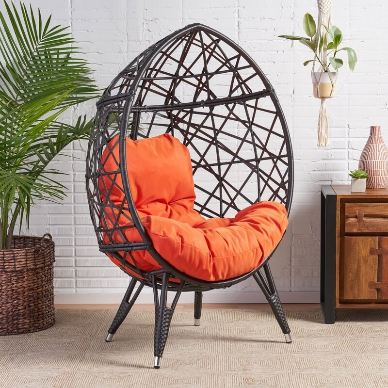 A teardrop-shaped egg chair with orange cushions and four legs