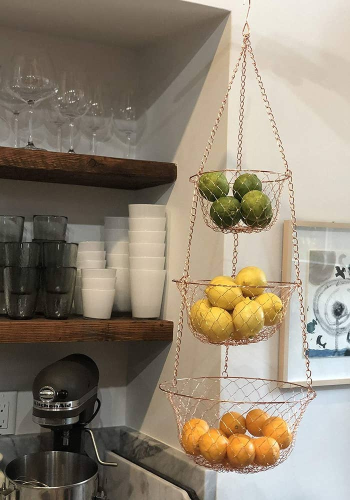 Three-tiered hanging basket displayed in a kitchen holding three different types of fruit in each basket