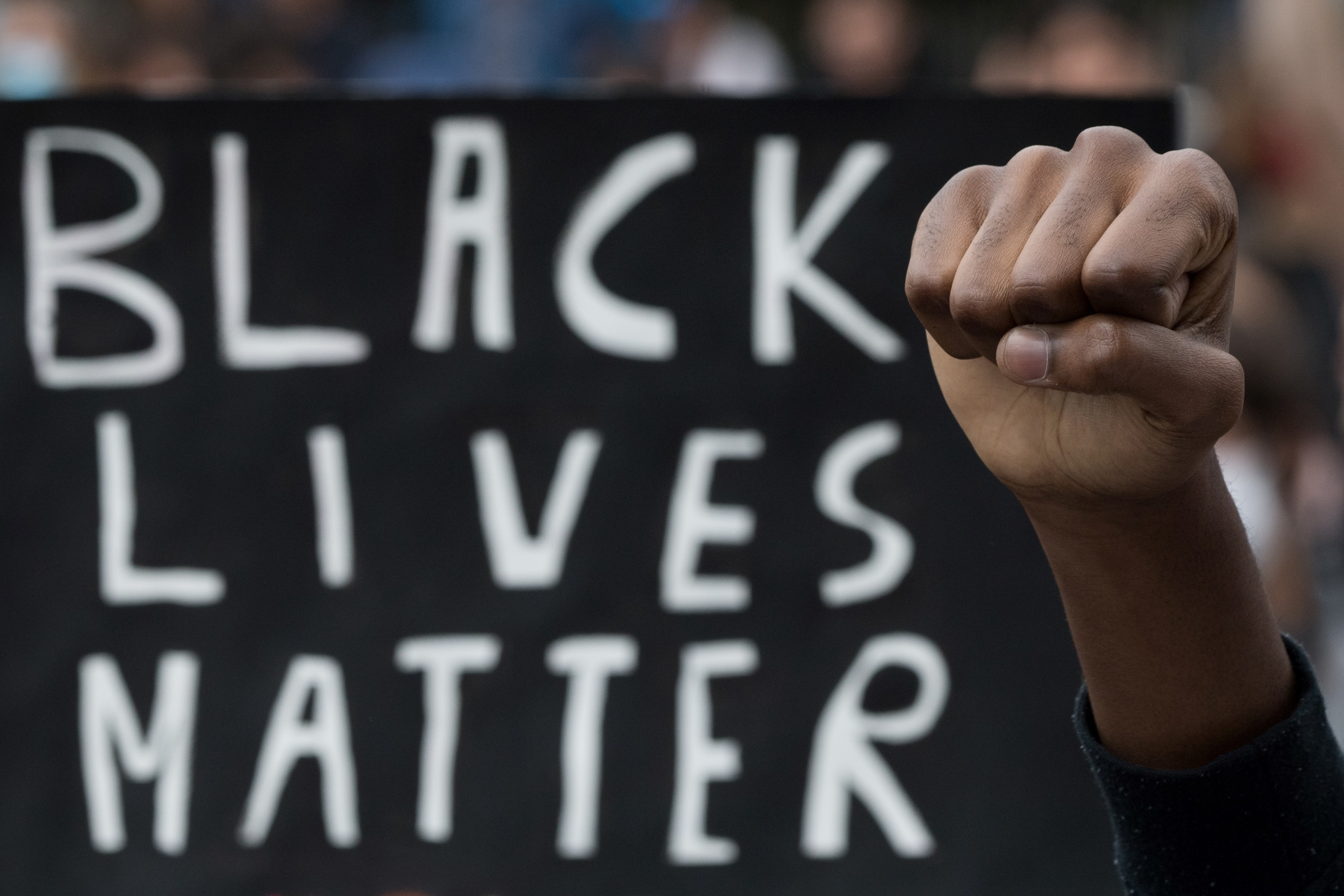 A Black person raises their fist in front of a Black Lives Matter protest sign 黒人の1人が「Black Lives Matter」と書かれた看板の前で、拳を掲げている。